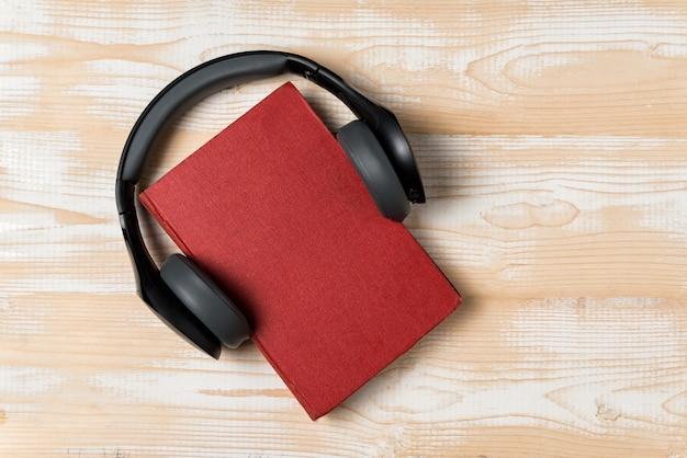 Cuffie e un libro. ascolta il libro concetto di audiolibro. vista dall'alto, copia spazio.