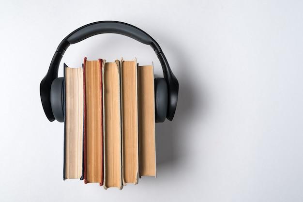 Cuffie indossate su una pila di vecchi libri su uno sfondo bianco. concetto di libreria audio. vista dall'alto