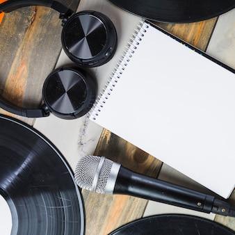 Cuffie; microfono; annotazione di vinile e blocco note a spirale in bianco sulla tavola di legno