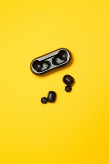 Cuffie senza fili su uno sfondo giallo. foto verticale