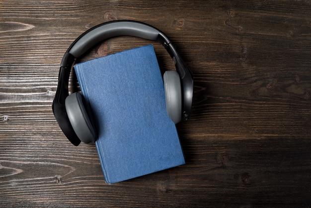 Cuffie sul libro. concetto di apprendimento audio. sfondo di legno scuro copia spazio, vista dall'alto