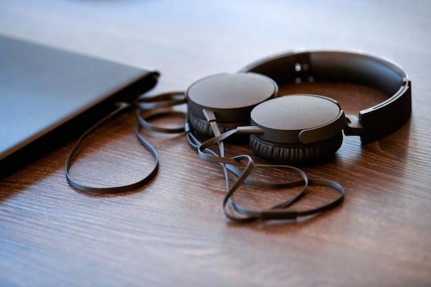 Cuffie sul tavolo dell'ufficio. cuffie collegate al computer portatile, copia spazio. ascoltare musica al lavoro