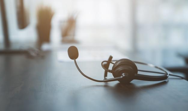 Cuffie voip dell'operatore telefonico dell'assistenza clienti sul posto di lavoro sulla scrivania.