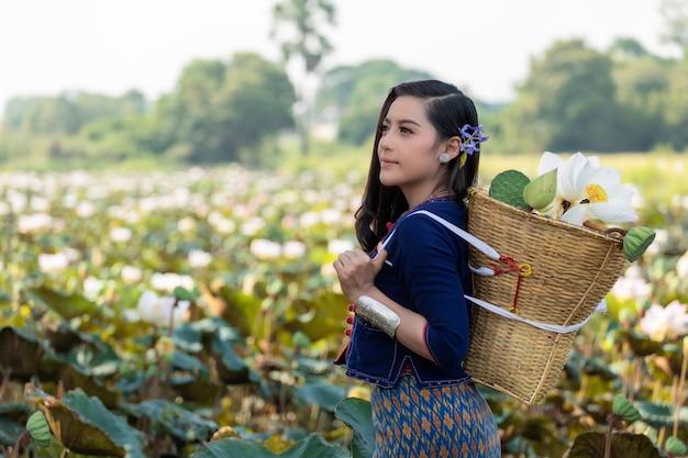 Cultura asiatica della tailandia dell'agricoltore delle donne con il vestito tradizionale dal loto.