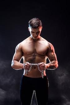 Culturista atletico bello dell'uomo di potere che fa gli esercizi con la catena, strappante. corpo muscoloso fitness su sfondo scuro. maschio perfetto. culturista fantastico, tatuaggio, posa.