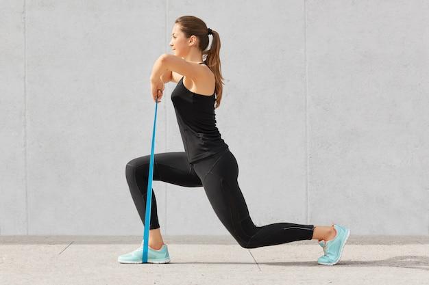 Culturista autodeterminato fa esercizi con l'elastico, lavora su mani e gambe, indossa comode scarpe da ginnastica e abbigliamento sportivo