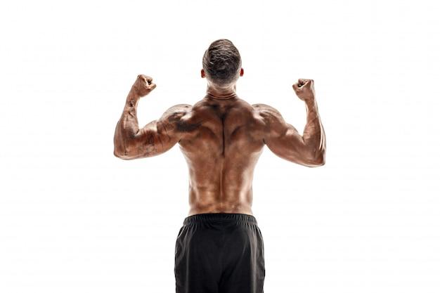 Culturista che mostra i suoi muscoli di schiena e bicipiti isolati su una scena bianca, istruttore di fitness personale