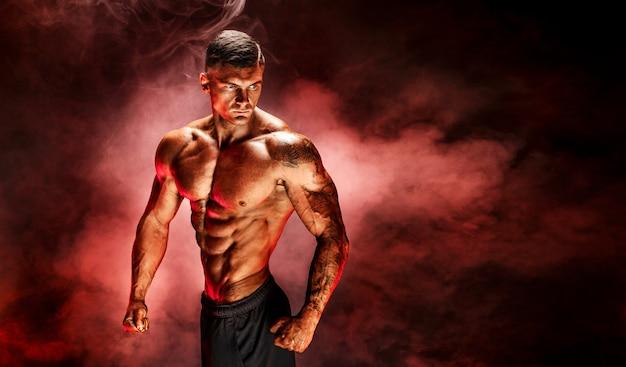 Culturista che posa uomo muscoloso tatuato forma fisica sulla scena rossa del fumo