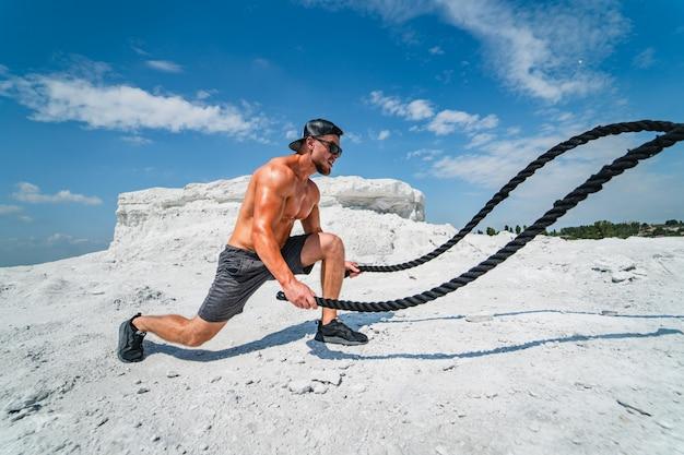 Culturista che si esercita con le corde di combattimento. giovane atletico che risolve con le corde di battaglia sulla natura