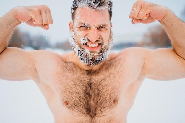 Culturista forte con la faccia e i capelli coperti di neve che dimostra i suoi muscoli