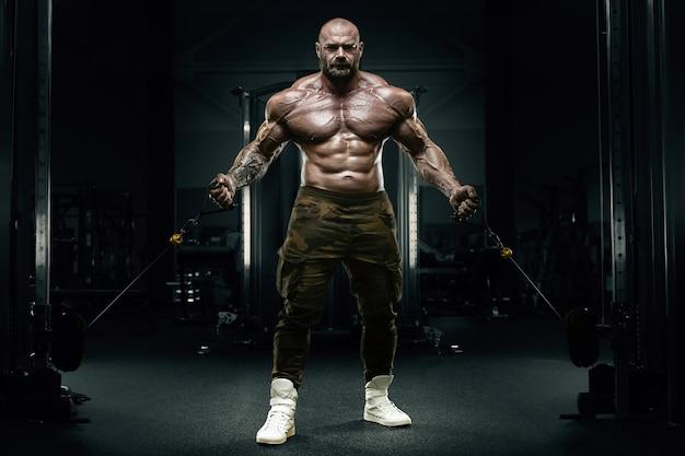 Culturista forte uomo atletico pompare i muscoli