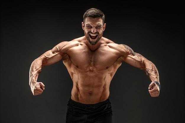 Culturista in posa. uomo muscoloso fitness sulla parete scura. ruggendo per la motivazione.