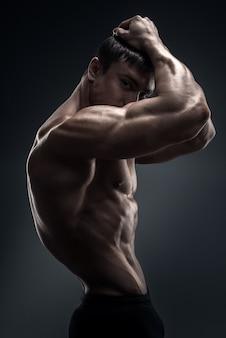 Culturista muscolare bello che posa sopra il fondo nero