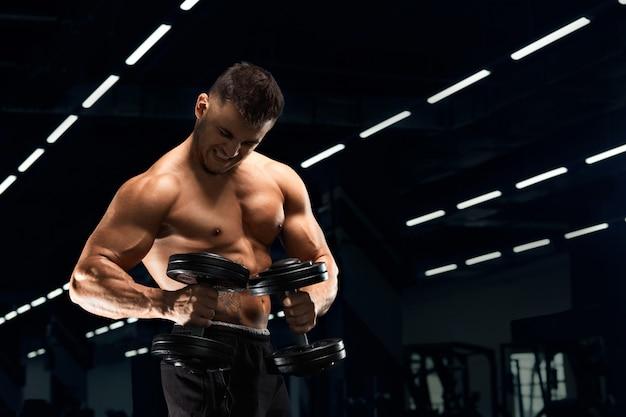 Culturista muscolare che fa esercizi con il manubrio in palestra l'uomo forte atletico mostra corpo, muscoli addominali, bicipiti e tricipiti. esercitati, ingrassando, pompando i muscoli con i manubri.