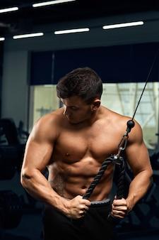 Culturista muscolare che fa esercizi sulla macchina del crossover via cavo in palestra l'uomo forte atletico mostra il corpo, i muscoli addominali, i bicipiti e i tricipiti.
