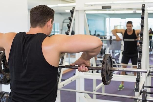 Culturista muscolare che solleva peso pesante nero del bilanciere che guarda in specchio