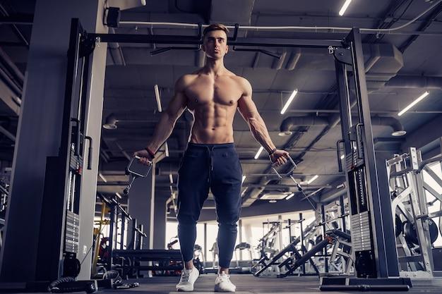 Culturista muscolare di forma fisica che fa esercizio pesante per i muscoli pettorali sulla macchina con cavo in palestra.