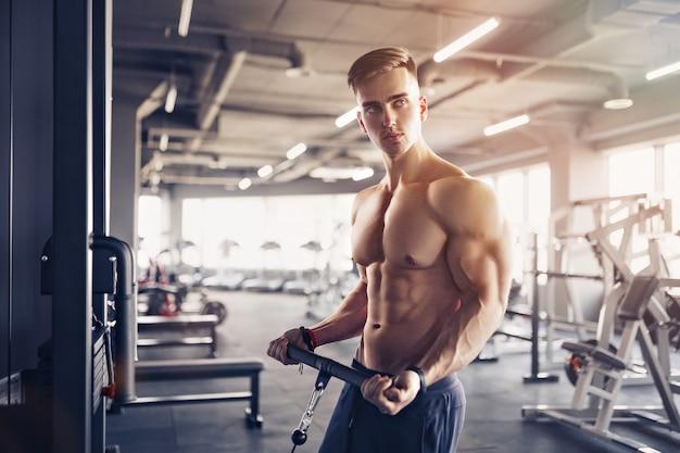 Culturista muscolare di forma fisica che fa esercizio pesante per il bicipite sulla macchina con cavo in palestra.