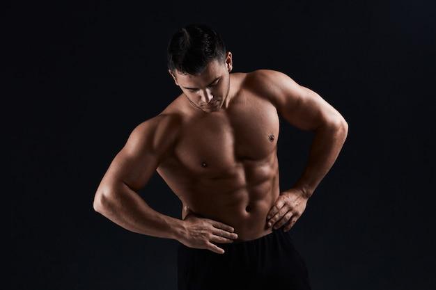 Culturista muscolare su nero. l'uomo atletico forte mostra corpo, muscoli addominali, muscoli toracici, bicipiti e tricipiti. bodybuilding.