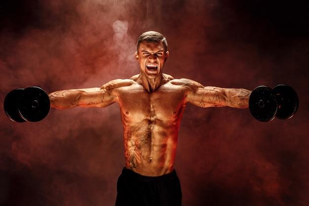 Culturista muscoloso molto muscoloso, esegui l'esercizio con manubri, sulla spalla muscolare deltoidea