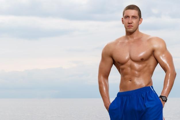 Culturista sexy sulla spiaggia