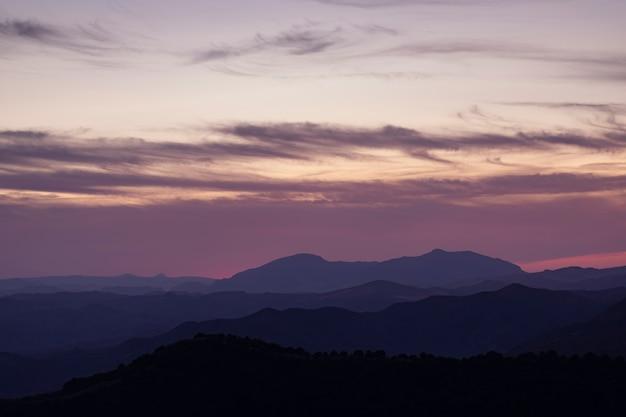 Cumuli di tramonto con il sole che tramonta su sfondo scuro