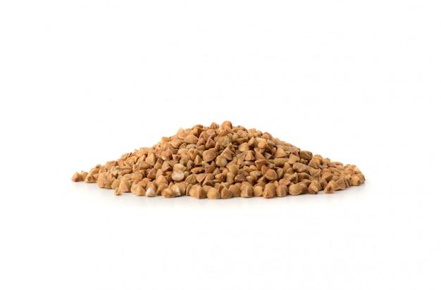 Cumulo di grano saraceno crudo secco in grani isolati su sfondo bianco.