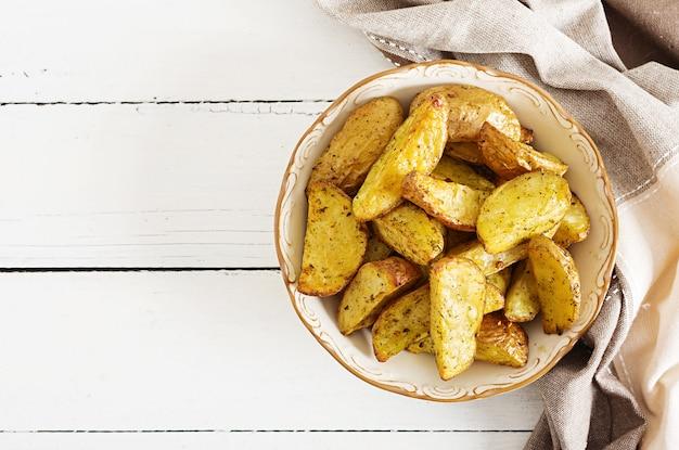 Cunei della patata al forno con aglio su un fondo bianco.