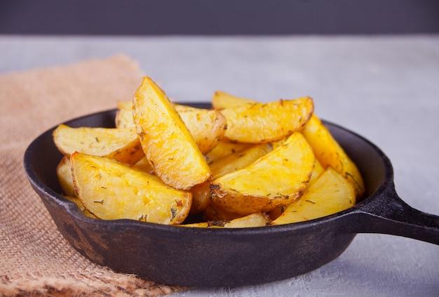 Cunei di patate al forno fatti in casa con erbe sulla padella di ferro nero su sfondo grigio.