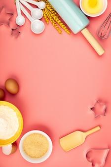 Cuocendo o cucinando gli ingredienti su fondo rosa, disposizione piana
