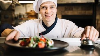 Cuocere con insalata su piastra suoneria campana di servizio