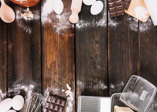 Cuocere gli ingredienti di una torta con utensili da cucina sul tavolo in legno