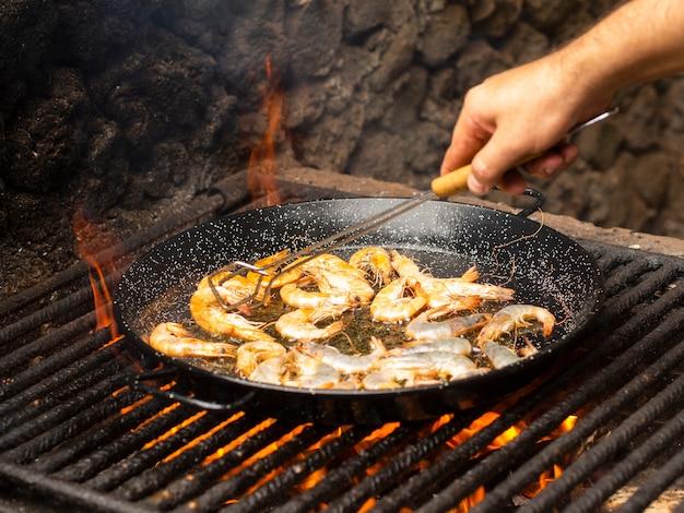 Cuocere i gamberi pieghevoli sulla padella
