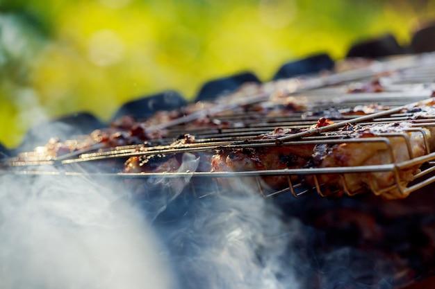 Cuocere i petti di pollo sulla griglia del barbque