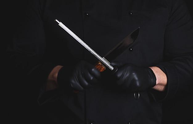 Cuocere in guanti di lattice neri affila un coltello