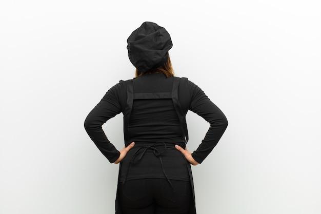Cuocere la donna sentirsi confusa o piena o dubbi e domande, chiedendosi, con le mani sui fianchi, vista posteriore