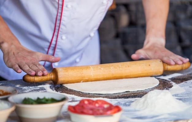 Cuocere la preparazione della pizza in un ristorante.