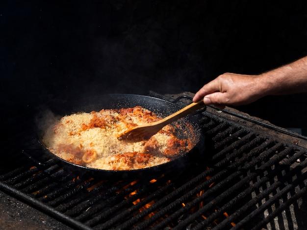 Cuocere mescolando il riso con anelli di calamari e verdure sulla padella