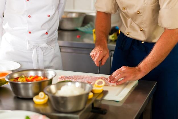 Cuochi che preparano pesce nella cucina del ristorante o dell'hotel