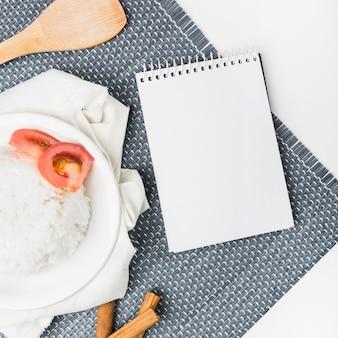 Cuocia a vapore il riso con il pomodoro sul piatto vicino al blocco note a spirale