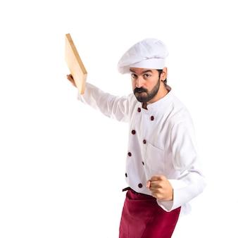 Cuoco che attacca con lo strumento della cucina