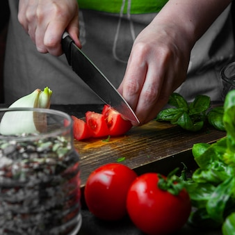 Cuoco che taglia pomodoro sul bordo di legno