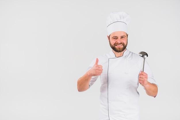 Cuoco del cuoco unico che gesturing pollice in su con la siviera