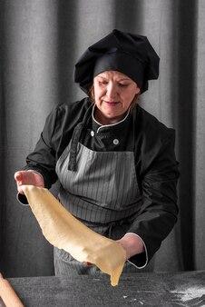 Cuoco femminile che tiene foglio di pasta