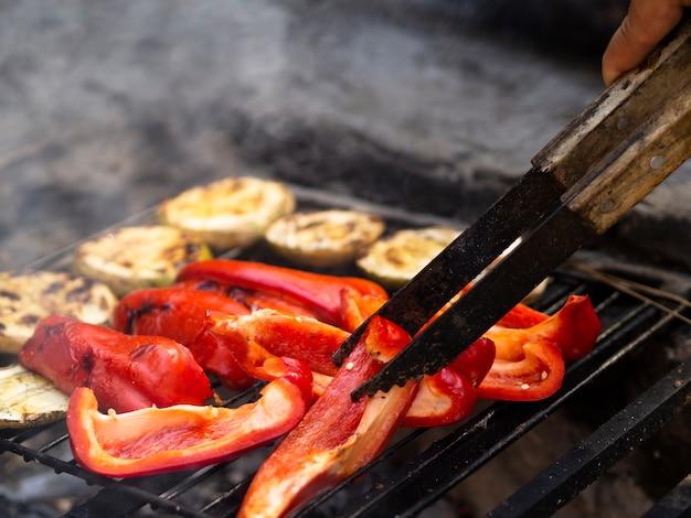 Cuoco irriconoscibile lanciando fette di peperone dolce sulla griglia del barbecue