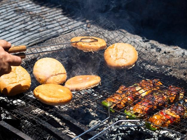 Cuoco irriconoscibile lanciando panini di hamburger che arrostiscono sulla griglia con le tenaglie