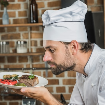 Cuoco maschio che odora il piatto preparato delizioso