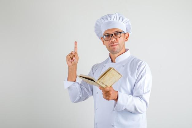 Cuoco maschio in cappello, uniforme e occhiali tenendo il libro e il pensiero