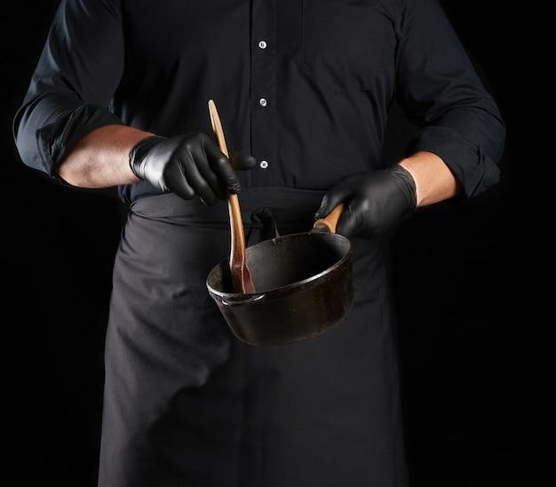Cuoco maschio in uniforme nera e guanti in lattice tiene una padella rotonda in ghisa nera vintage vuota