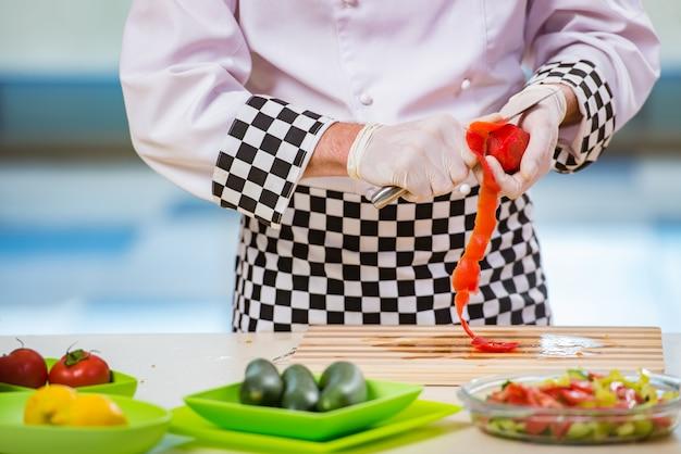 Cuoco maschio prepara il cibo in cucina